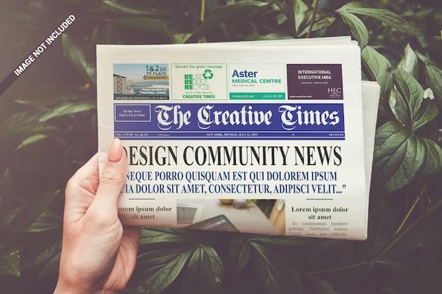 Folded newspaper in hand mockup Premium Psd
