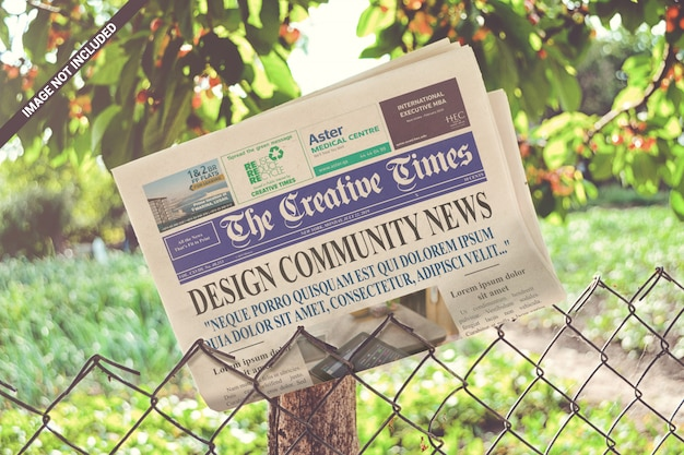 Folded newspaper on the metallic fence mockup Premium Psd