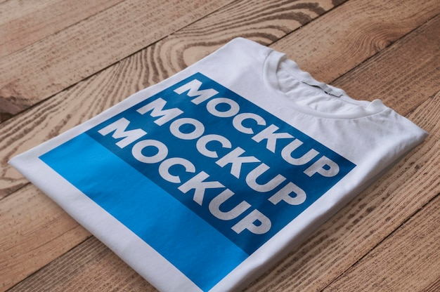 목재 표면 모형 위에 접힌 흰색 티셔츠 무료 PSD 파일