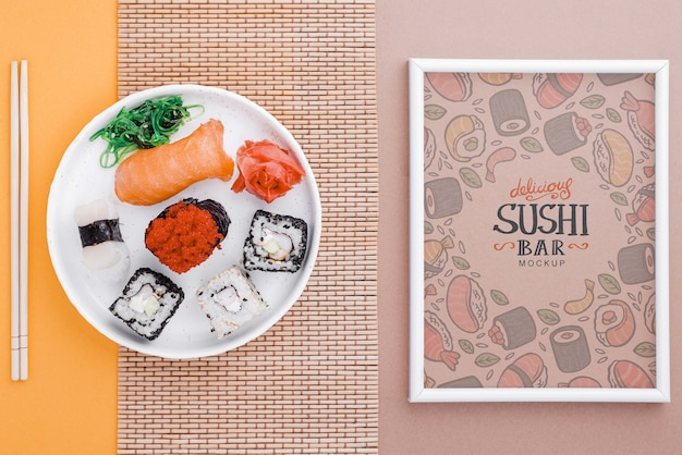 Frame beside plate with sushi rolls on table Free Psd