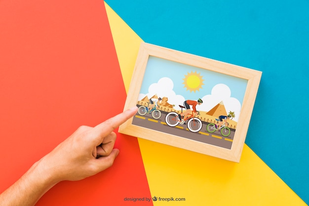 Frame mock up with pointing finger Free Psd