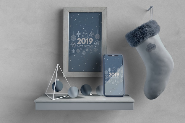 Frame and sock on wall above shelf with phone Free Psd
