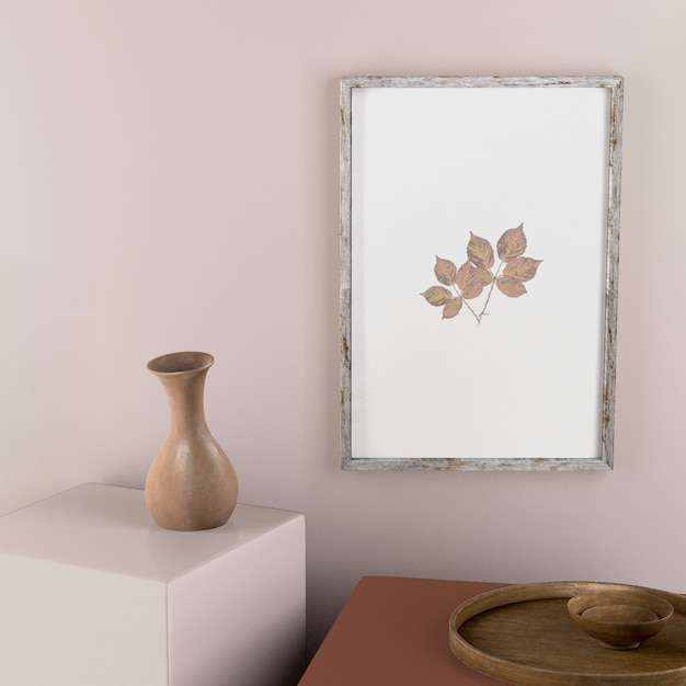 Frame on wall with leaves and vase decor Free Psd