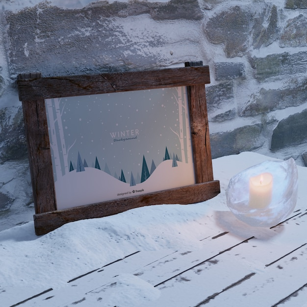 Frame with winter theme beside wall Free Psd