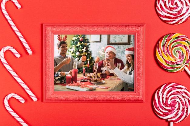 Семейное фото в рамке с сахарными тростниками и леденцами Бесплатные Psd