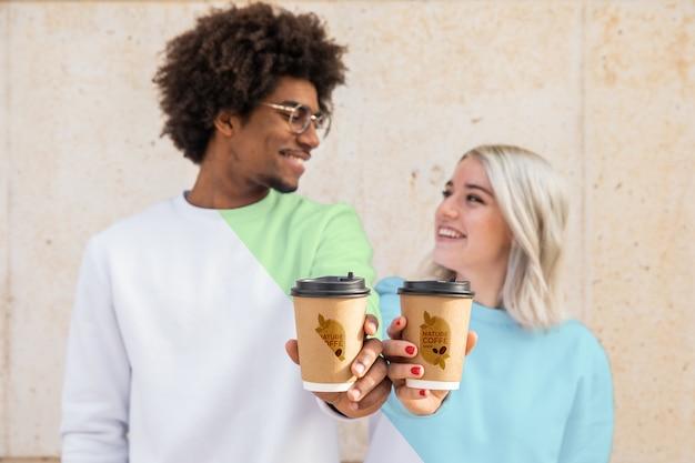 Amici che indossano felpe con cappuccio e bere caffè Psd Gratuite