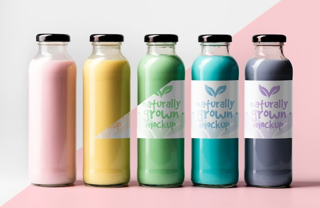 Front view of assortment of transparent juice bottles with cap Free Psd
