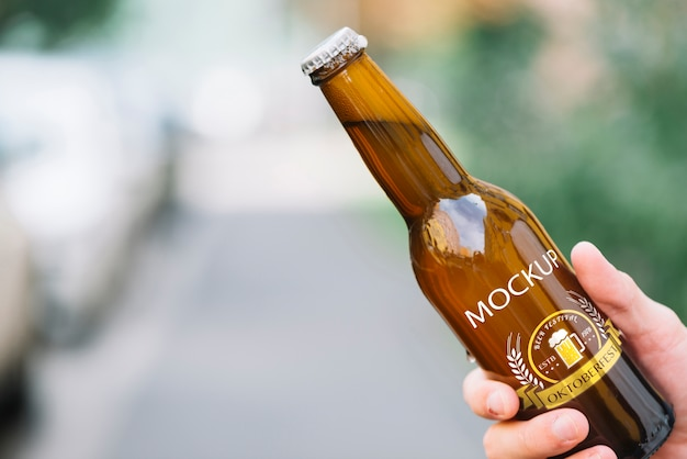 Front view beer bottle held by person Free Psd