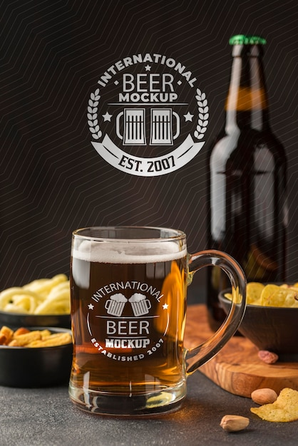 Front view of beer pint and bottle with assortment of snacks Free Psd