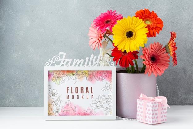 Vista frontale del bouquet di margherite con cornice e regalo Psd Gratuite