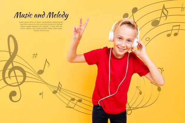 Vista frontale del bambino che ascolta la musica sulle cuffie e che fa il segno di pace Psd Gratuite