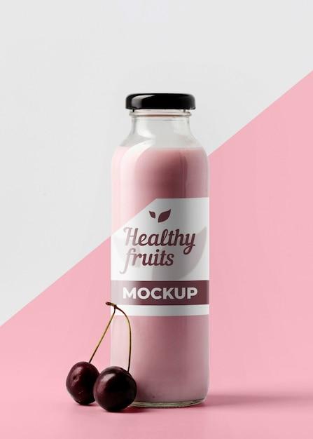 Vista frontale della bottiglia di succo trasparente con ciliegie Psd Gratuite