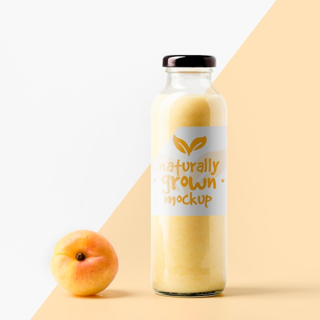Front view of clear juice bottle with peach and cap Free Psd