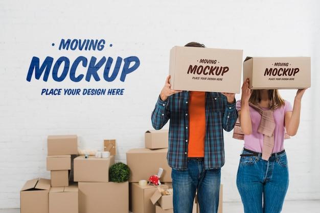Vista frontale della coppia in posa con scatole in movimento mock-up Psd Gratuite