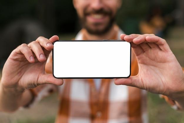Vista frontale dell'uomo di smiley defocused che tiene smartphone durante il campeggio Psd Gratuite