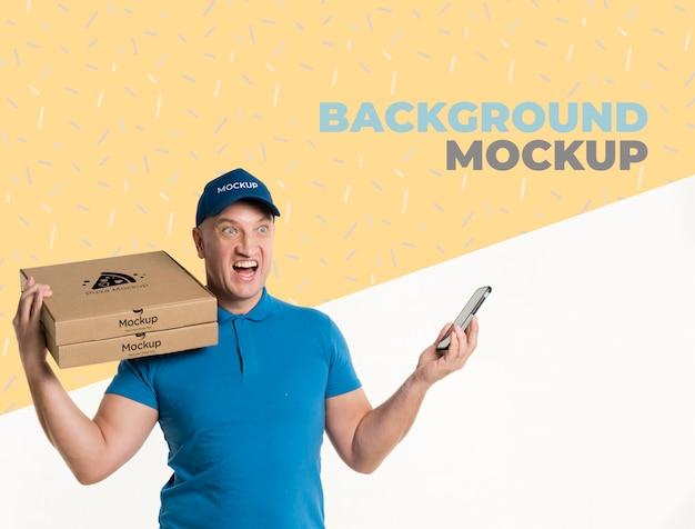 Uomo di consegna di vista frontale che tiene un modello di scatole per pizza Psd Gratuite