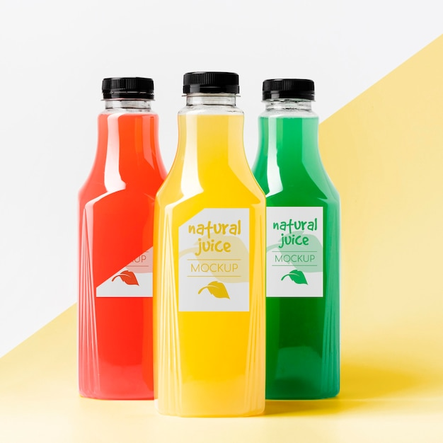 Front view of different clear juice bottles with caps Free Psd