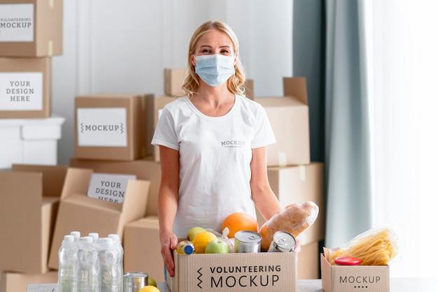 Vista frontale del volontario femminile con maschera medica che prepara donazioni di cibo Psd Gratuite