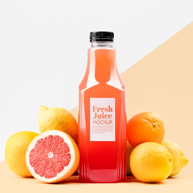 Front view of glass juice bottle with grapefruit and lemons Free Psd