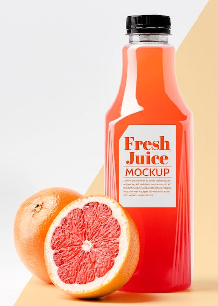Front view glass juice bottle with grapefruit Free Psd