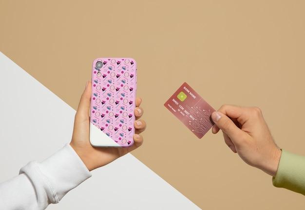 Vista frontale dello smartphone e della carta di credito tenuti in mano Psd Gratuite