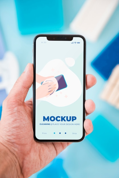 Front view of hand holding smartphone with cleaning Premium Psd