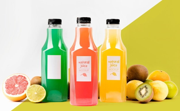Front view of juice bottles with grapefruit and kiwi Free Psd