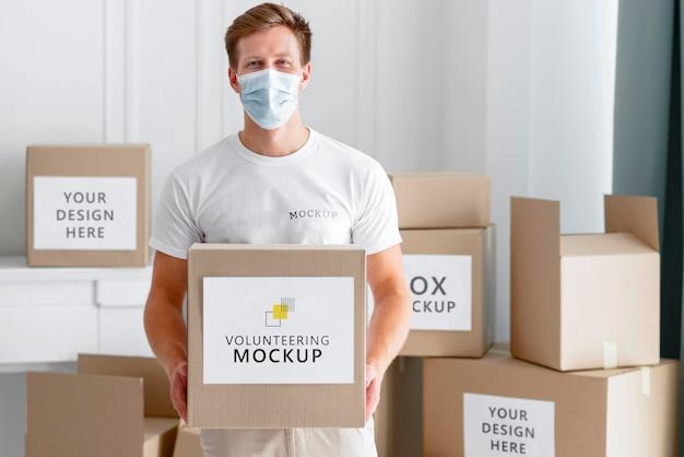Vista frontale del volontario maschio con maschera medica che tiene scatola di donazione di cibo Psd Gratuite