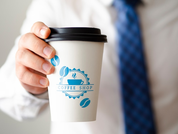 Front view man holding a cup of coffee mock-up Premium Psd