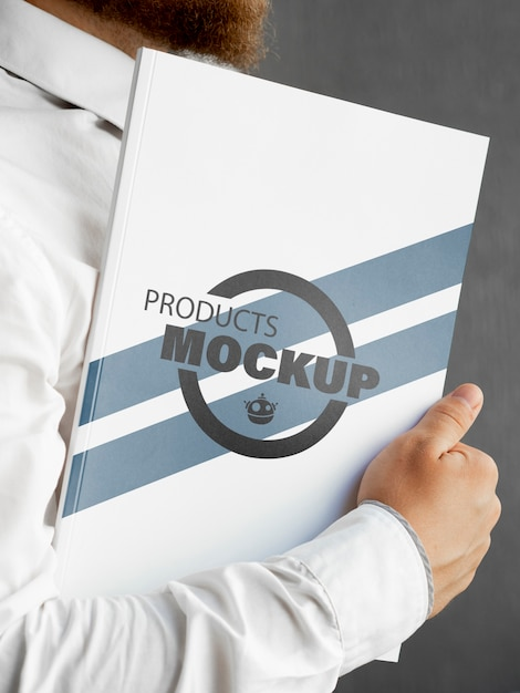 Front view man holding a notebook mock-up Free Psd
