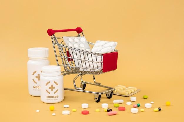 Vista frontale di bottiglie di medicina con pillole e carrello Psd Gratuite