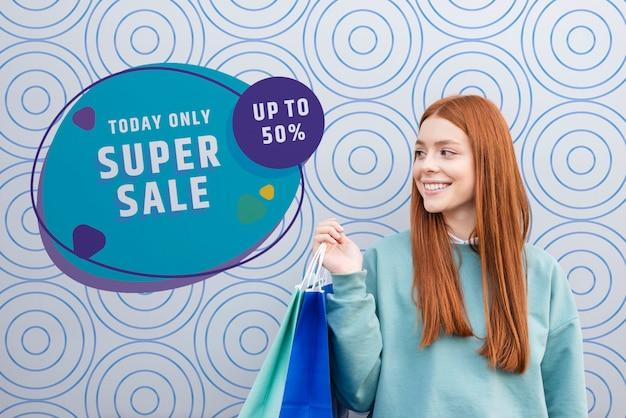 Вид спереди средний снимок женщины, улыбаясь и держа бумажные пакеты Бесплатные Psd