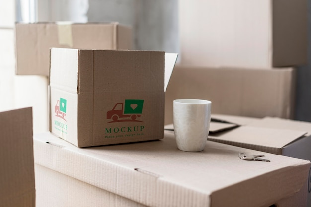 Front view moving house boxes and cup of coffee Premium Psd