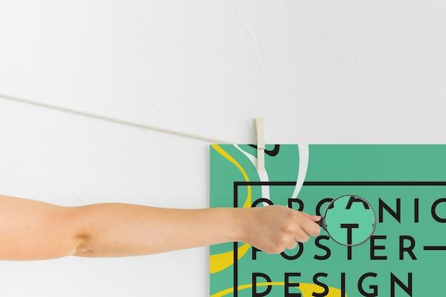 Вид спереди рука держит увеличительное стекло над плакатом Бесплатные Psd