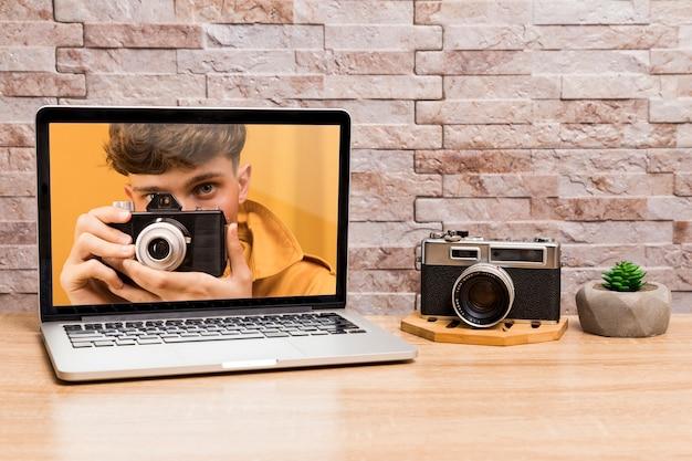 Вид спереди ноутбука и камеры на столе Бесплатные Psd