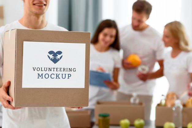 Вид спереди мужского добровольца, держащего коробку с пожертвованиями Бесплатные Psd