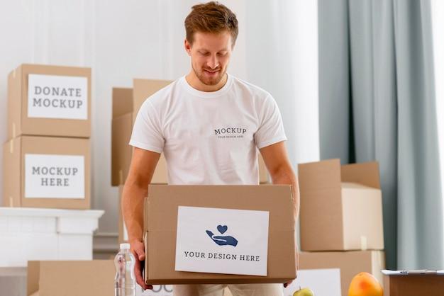 Вид спереди мужского добровольца, держащего ящик для пожертвований Бесплатные Psd