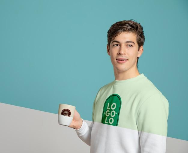 Вид спереди человека в свитере, держащего кружку Бесплатные Psd