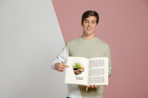 Вид спереди человека, указывая на книгу, которую он держит Бесплатные Psd