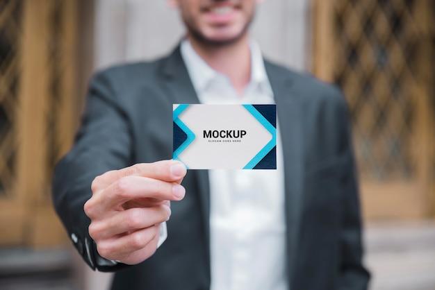 ビジネスカードを持っている笑顔の実業家の正面図 Premium Psd