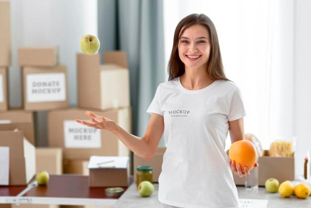 Вид спереди смайлика-добровольца, подбрасывающего яблоко в воздухе Бесплатные Psd