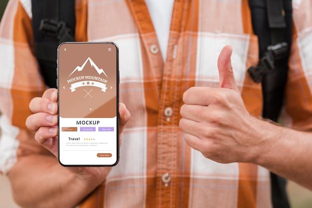 스마트 폰을 들고 캠핑하는 동안 엄지 손가락을 포기하는 웃는 남자의 전면보기 무료 PSD 파일