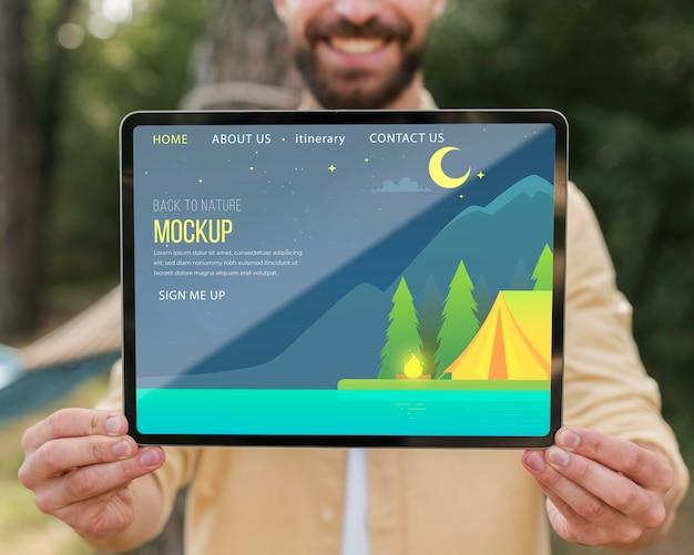 キャンプ中にタブレットを保持しているスマイリー男の正面図 Premium Psd