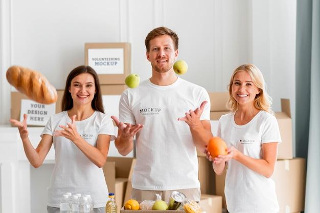 Вид спереди смайликов-волонтеров, готовящих коробки с едой для пожертвования Бесплатные Psd