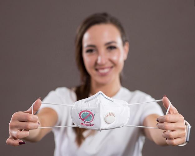 Вид спереди смайлика женщины, держащей маску Бесплатные Psd