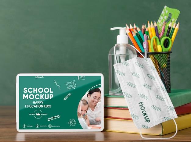 Вид спереди планшета со школьными принадлежностями и медицинской маской на день образования Premium Psd