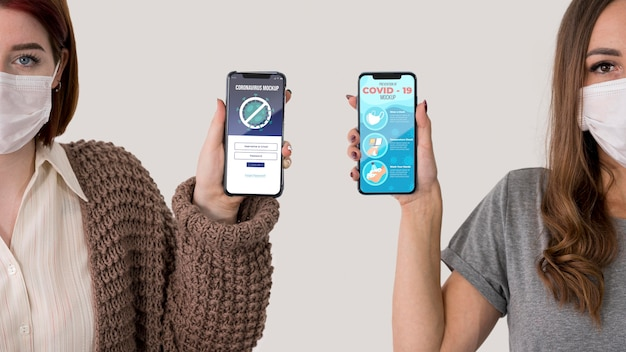 Вид спереди двух женщин в масках, держащих смартфоны Бесплатные Psd