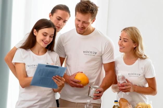 Вид спереди добровольцев, проверяющих блокнот с пожертвованиями Бесплатные Psd
