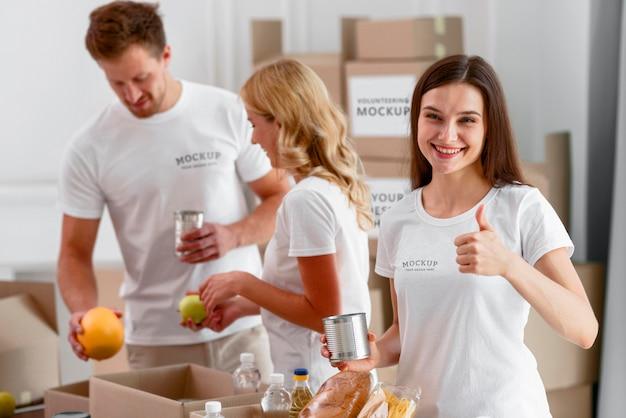 Вид спереди добровольцев, держащих продукты для пожертвований и поднимающих пальцы вверх Бесплатные Psd