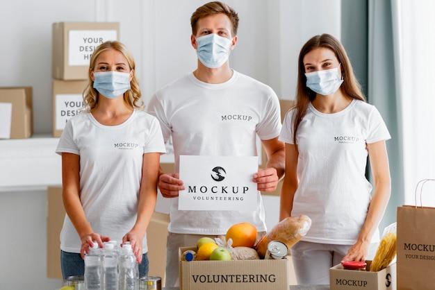 Вид спереди добровольцев в медицинских масках, держащих чистый лист бумаги рядом с коробкой для еды Бесплатные Psd